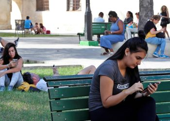 Varias personas usan sus teléfonos móviles en un parque con conexión a Internet mediante wifi pública, el 27 de diciembre de 2018, en La Habana. Foto: Ernesto Mastrascusa / EFE.