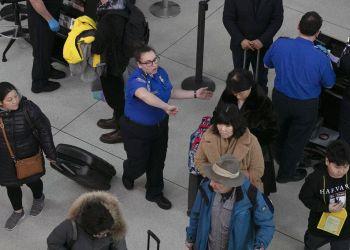 Una agente de la Administración de Seguridad en el Transporte, centro, da instrucciones a los pasajeros en un punto de revisión en el Aeropuerto Internacional John F. Kennedy, en Nueva York. Foto: Mark Lennihan / AP.