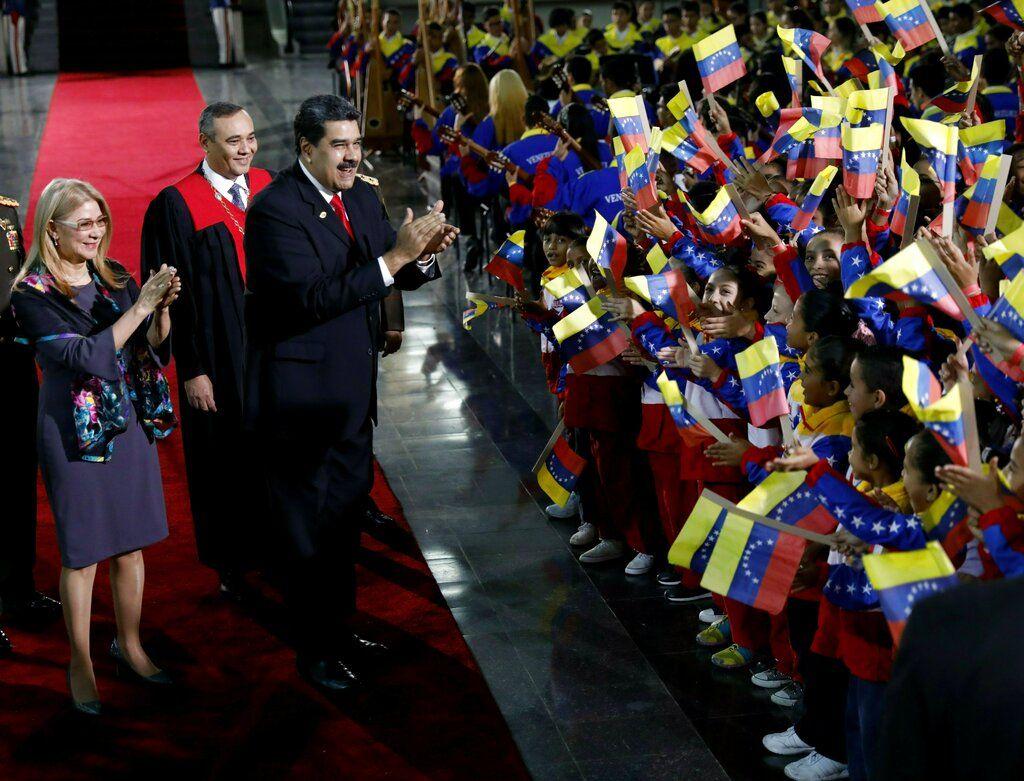 Nicolás Maduro, y la primera dama, Cilia Flores, se detienen para saludar a los niños que agitan la bandera al llegar a la ceremonia de juramentación en el Tribunal Superior de Justicia. Foto: Ariana Cubillos / AP.
