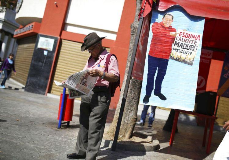 """Un partidario del gobierno venezolano lee el periódico junto a un cartel con la imagen del exfallecido presidente Hugo Chávez con el lema """"Esquina caliente, Maduro presidente"""", en Caracas, Venezuela, el 29 de enero de 2019. (AP Foto/Rodrigo Abd)"""