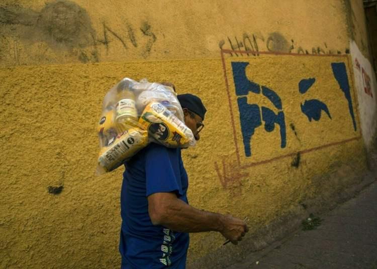 El venezolano Carlos González lleva una bolsa con alimentos entregada por el gobierno a los más pobres, en el barrio Antimano de Caracas, 29 de enero de 2019. Foto: Rodrigo Abd / AP.