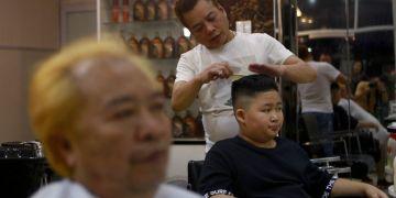 A Le Phuc Hai de 66 años, izquierda, y To Gia Huy, de 9 años, les cortan el cabello al estilo Trump y Kim en Hanoi, Vietnam, el martes 19 de febrero de 2019. Foto: Hau Dinh / AP.