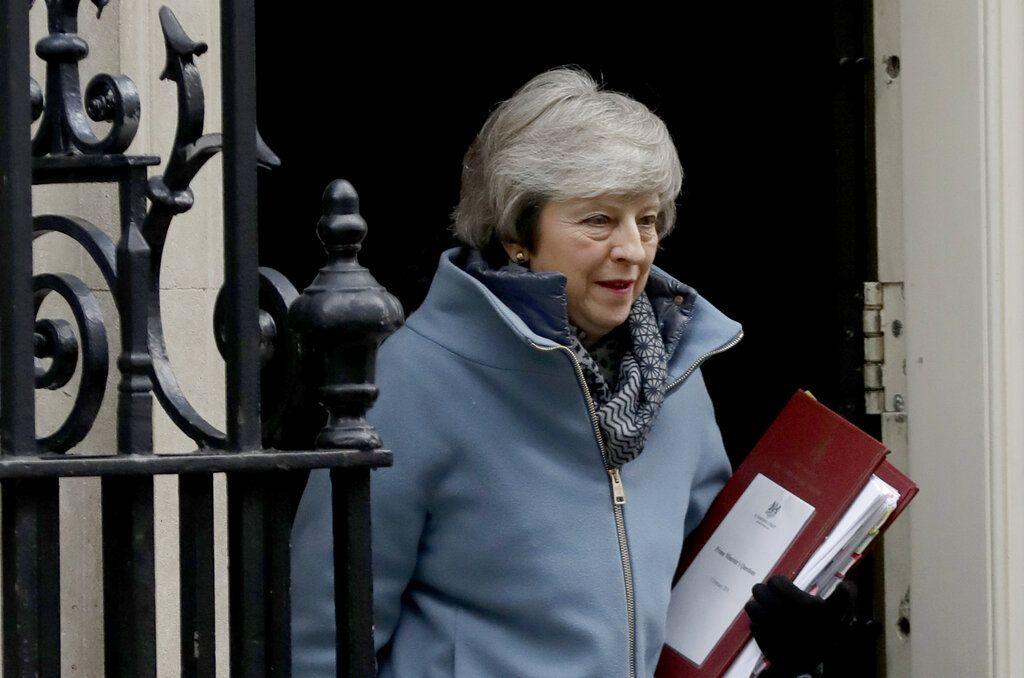 La primera ministra de Gran Bretaña, Theresa May, sale de su residencia oficial en el 10 Downing Street, Londres, para asistir a una sesión de control en el parlamento británico. Foto: Matt Dunham / AP.