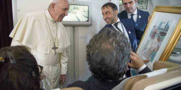 El Papa Francisco recibe un regalo de un periodista a bordo del avión papal cuando viaja de Abu Dabi a Roma el 5 de febrero del 2019. Foto: Luca Zennaro / Pool vía AP.