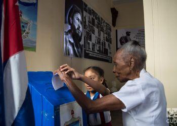 Una señora débil visual vota en un colegio electoral de la Habana Vieja, auxiliada por una niña, en el referendo constitucional cubano el 24 de febrero de 2019. Foto: Otmaro Rodríguez.