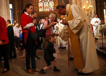 Sacerdotes dan la comunión a los feligreses durante la misa del domingo de Pascua en la grandiosa iglesia Saint-Eustache en París, el domingo 21 de abril de 2019. Foto: Francisco Seco/AP.
