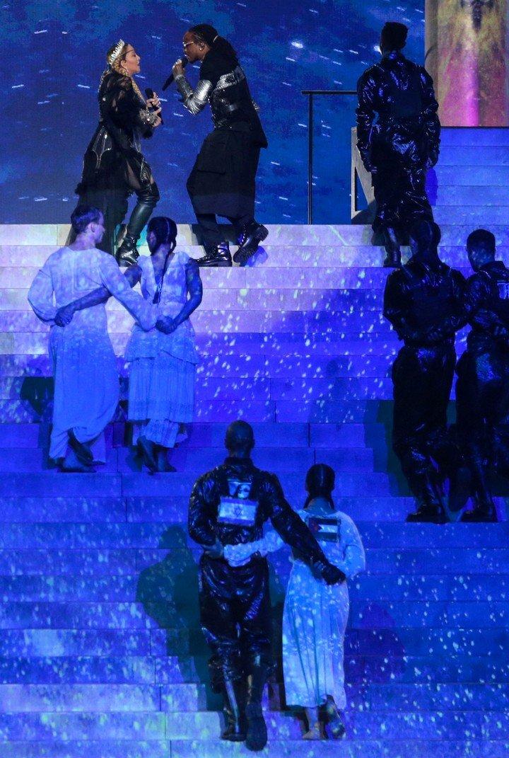 Los bailarines abrazados con las banderas israelí y palestina en sus espaldas. Foto: AFP.