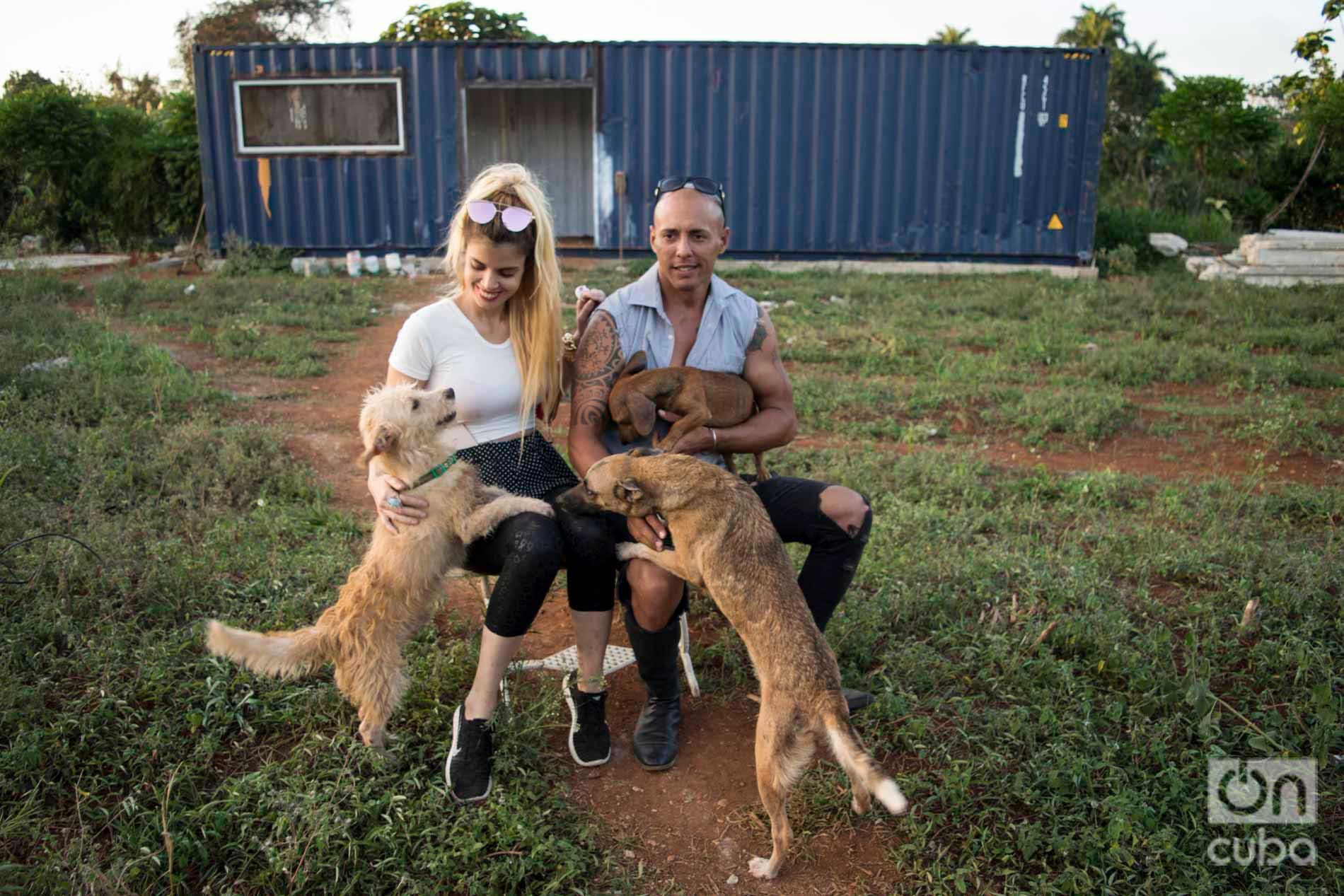 Venus y Ernesto con varios de los perros de su refugio. Detrás, el contenedor que adaptarán como casa mientras construyen su nueva vivienda. Foto: Otmaro Rodríguez.