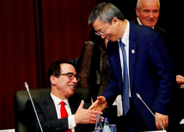 El gobernador del Banco Central de China, Yi Gang, estrecha la mano del secretario del Tesoro de Estados Unidos, Steve Mnuchin (izquierda), durante la cumbre de ministros de Finanzas y gobernadores de bancos centrales del G20, en Fukuoka, Japón, el 8 de junio de 2019. Foto: Kim Kyung-hoon / Pool Photo vía AP.
