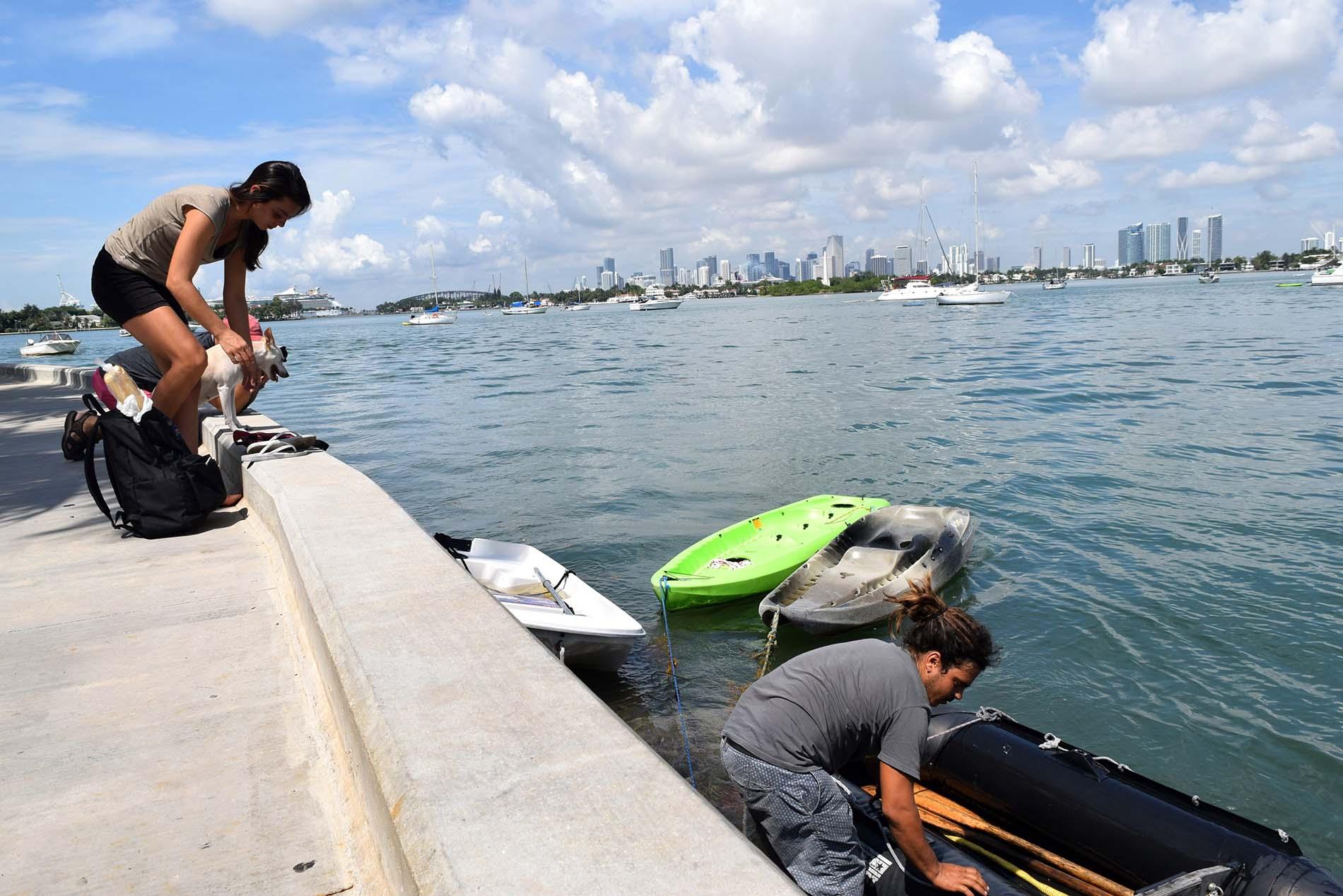 La española Lara Gandía y el cubano David Berenguer, acompañados de su perra Lila en la Bahía Vizcaína de Miami, Florida. Foto: Jorge Ignacio Pérez / EFE.