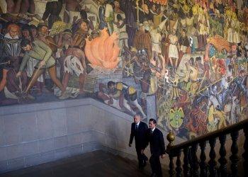 El presidente mexicano Enrique Peña Nieto camina el 9 de agosto de 2018 con el entonces presidente electo Andrés Manuel López Obrador frente a un mural de Diego Rivera en el Palacio Nacional, México. Foto: Oficina de prensa presidencial de México vía AP.