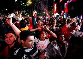 Numerosos aficionados festejan en Jurassic Park, afuera de la Arena Scotiabank en Toronto la victoria de los Raptors de Toronto por 114-110 sobre los Warriors de Golden State en el sexto partido para conquistar el título de la NBA de visitantes en Oakland, California. (Nathan Denette/The Canadian Press vía AP)