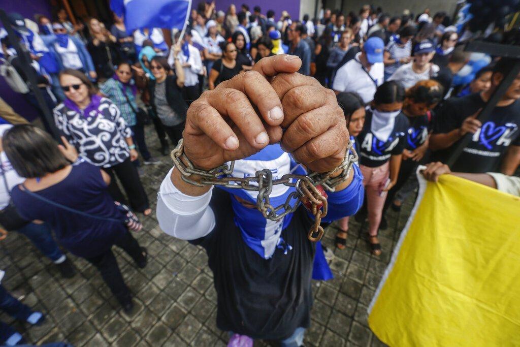 Un hombre enseña sus muñecas encadenadas durante un evento para conmemorar el primer aniversario de una campaña de represión del gobierno nicaragüense, en Managua, Nicaragua, el jueves 30 de mayo de 2019. Foto: Alfredo Zúñiga / AP.
