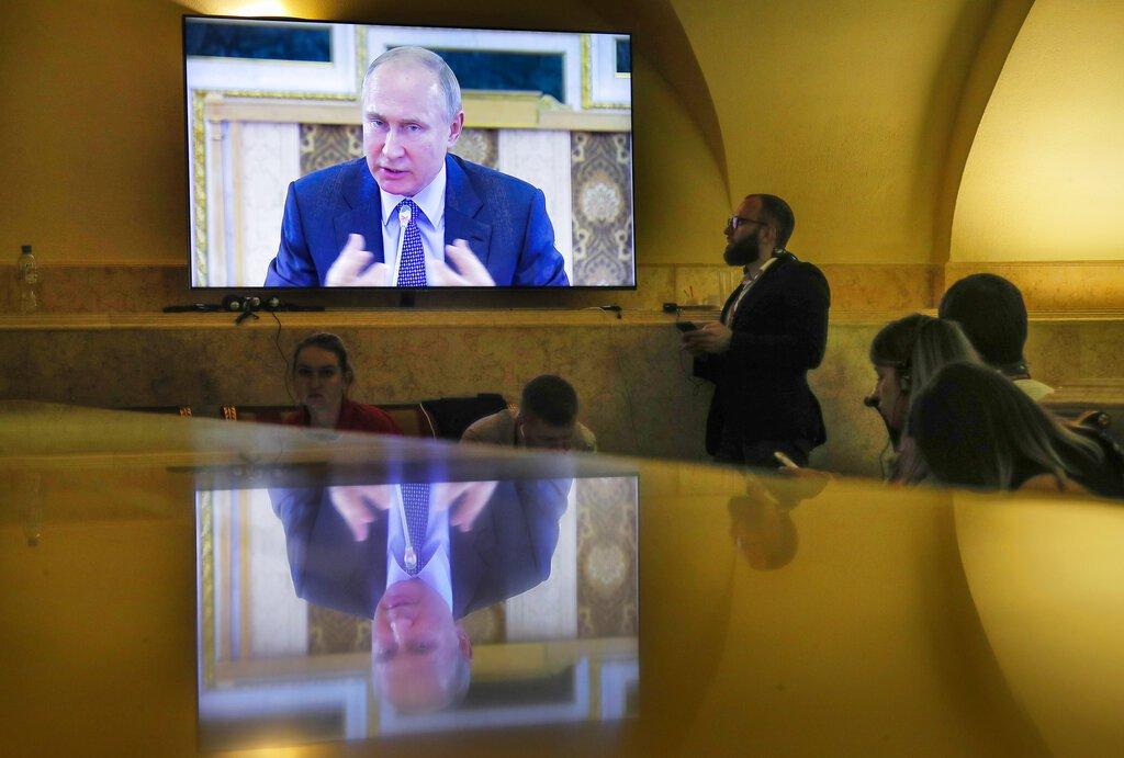 Periodistas observan una pantalla donde se ve al presidente ruso Vladimir Putin en una reunión con jefes de agencias de noticias internacionales en el Foro Económico Internacional en San Petersburgo, Rusia, el jueves 6 de junio de 2019. (AP Foto/Dmitri Lovetsky)