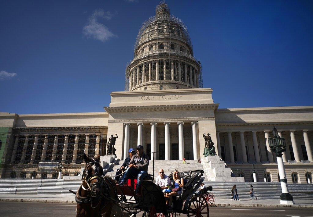 En esta foto del 18 de enero de 2018, los turistas viajan en un carro tirado por caballos que pasa por el edificio del Capitolio, en La Habana, Cuba. Foto: Ramón Espinosa / AP / Archivo.