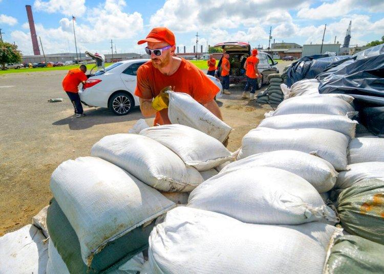 Trabajadores reclusos del departamento de policía de la municipalidad de St. Bernard trasladan costales de arena para los residentes en Chalmette, Luisiana, el jueves 11 de julio de 2019. Foto: Matthew Hinton / AP.
