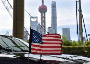 Una bandera de Estados Unidos ondea en un auto del consulado, delante de los edificios del distrito financiero de Lujiazui, en el exterior del hotel donde se alojan los negociadores comerciales de EEUU durante los contactos con sus homólogos chinos, en Shanghái, el 31 de julio de 2019. Foto: Greg Baker/Pool vía AP.