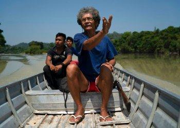 En esta imagen, tomada el 27 de agosto de 2019, Wakonkra Kayapo de la comunidad indígena kayapó, marca el camino a seguir por el río Curua mientras busca a supuestos especuladores y madereros en la reserva indígena de Bau, en Altamira, en la Amazonía brasileña, cerca de una zona de incendios. Foto: Leo Correa/AP.