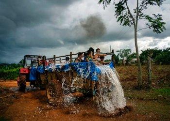 Un tractor hala un remolque que fue convertido en una piscina a lo largo de las calles del vecindario de El Infernal, en la provincia de Pinar del Río, Cuba. Foto: Ramon Espinosa/AP.