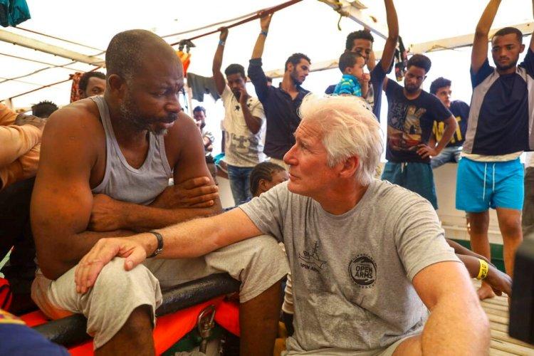 El actor Richard Gere, derecha, habla con migrantes al bordo del buque humanitario Open Arms durante el cruce del Mediterráneo, viernes 9 de agosto de 2019. (AP Foto/Valerio Nicolosi)