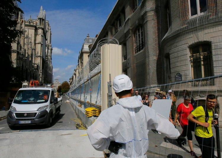 Un trabajador vestido con un overol blanco abre la puerta de la cerca que rodea a la catedral de Notre Dame, en París, el jueves 1 de agosto de 2019, mientras comienzan las labores preliminares para reparar los daños del incendio. Foto: Michel Euler / AP.