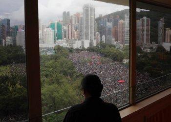 Una persona mira por una ventana a miles de manifestantes en el Parque Victoria en Hong Kong el domingo 18 de agosto del 2019. Foto: Kin Cheung / AP.