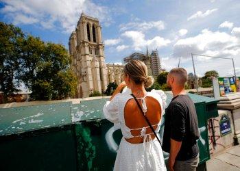Unos turistas observan la catedral de Notre Dame antes del inicio de una gran descontaminación de plomo en París, Francia. Foto: Francois Mori / AP.