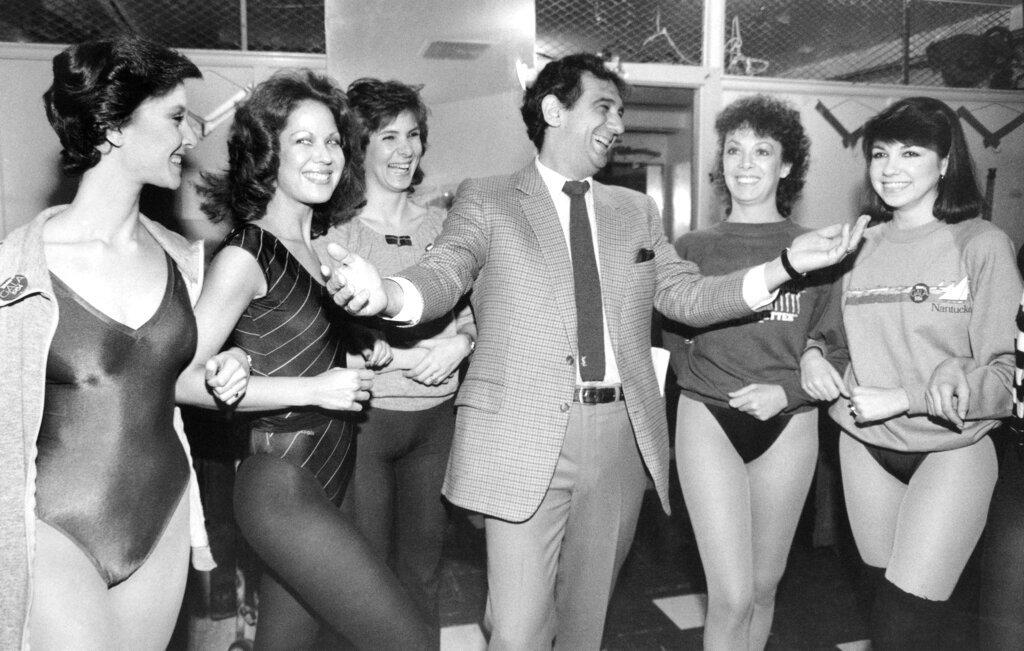 """En esta imagen de archivo del 27 de febrero de 1984, el cantante Plácido Domingo ríe con miembros de las Rockettes en el Radio City Music Hall de Nueva York. El cantante y las bailarinas coincidieron en el ensayo para la """"Gala of Stars 1984"""" del Canal 13. Foto: Steve Friedman / AP / Archivo."""