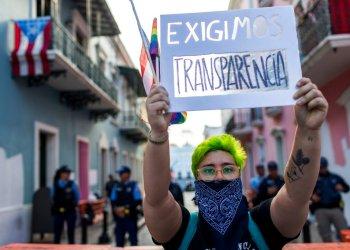 Un joven sostiene en lo alto un cartel durante una pequeña manifestación frente a La Fortaleza, la mansión del gobierno, en San Juan, Puerto Rico, el viernes 9 de agosto de 2019. (AP Foto/Dennis M. Rivera Pichardo)