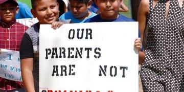 """En esta fotografía de archivo del 11 de agosto de 2019, menores hijos de padres latinos sostienen un cartel en apoyo a sus progenitores y de las personas arrestadas durante una redada contra los inmigrantes no autorizados en una planta procesadora de carne, en Catón, Missouri. El letrero dice """"Nuestros padres no son delincuentes"""". Foto: Rogelio V. Solis/ archivo AP."""