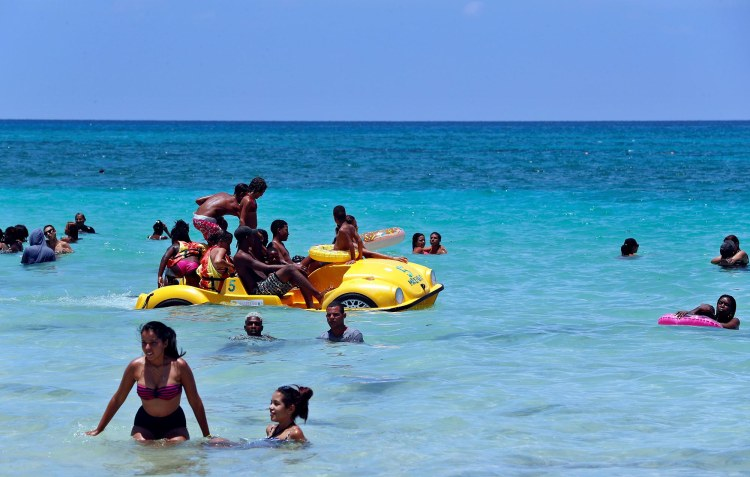 Un grupo de personas disfruta de un día de playa este verano en La Habana. Foto: Ernesto Mastrascusa / EFE.