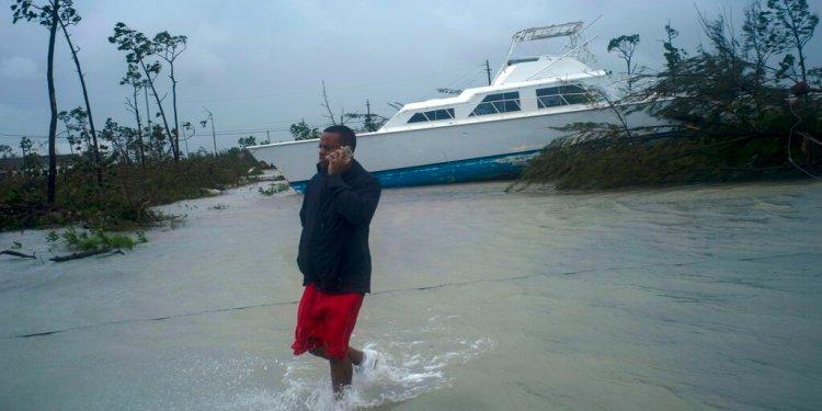 Un hombre habla por teléfono junto a una embarcación varada por el huracán Dorian cerca de la autopista cerrada en Freeport, Gran Bahama, Bahamas, el martes 3 de septiembre de 2019. (AP Foto/Ramón Espinosa)