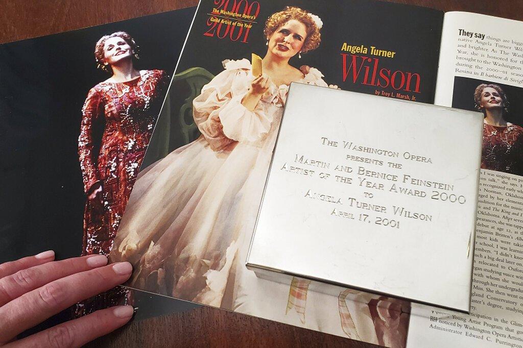 """En esta imagen, tomada el 2 de septiembre de 2019 y proporcionada por la cantante de ópera Angela TurnerWilson, muestra su premio a la mejor artista del año en 2000 de la Ópera de Washington, junto a una foto en la que aparece durante una presentación de """"El Cid"""" en 1999 (izquierda), y un artículo en una revista de la Ópera, en su casa en Texas. Foto: Cortesía de Angela TurnerWilsonvía AP."""