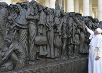 El Papa Francisco junto a una escultura de bronce que muestra a migrantes en un bote abarrotado, en la plaza de San Pedro, en el Vaticano, el 29 de septiembre de 2019. Foto: @aciprensa / Twitter.