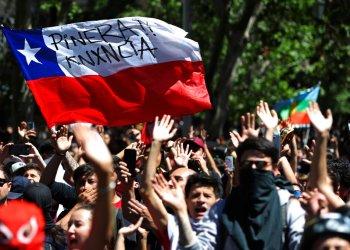 """Los manifestantes ondean una bandera chilena pintada con el mensaje """"Piñera renuncia"""" durante una manifestación en Santiago, Chile, el lunes 21 de octubre de 2019. (AP Foto / Miguel Arenas)"""