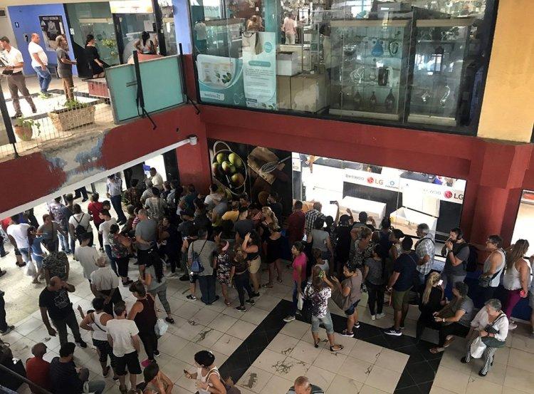 Personas hacen cola en el centro comercial Galerías de Paseo, en La Habana, en el que este 28 de octubre de 2019 comenzó la venta de equipos electrodomésticos en divisas a través de tarjetas magnéticas asociadas a cuentas bancarias. Foto: Ernesto Mastrascusa / EFE.
