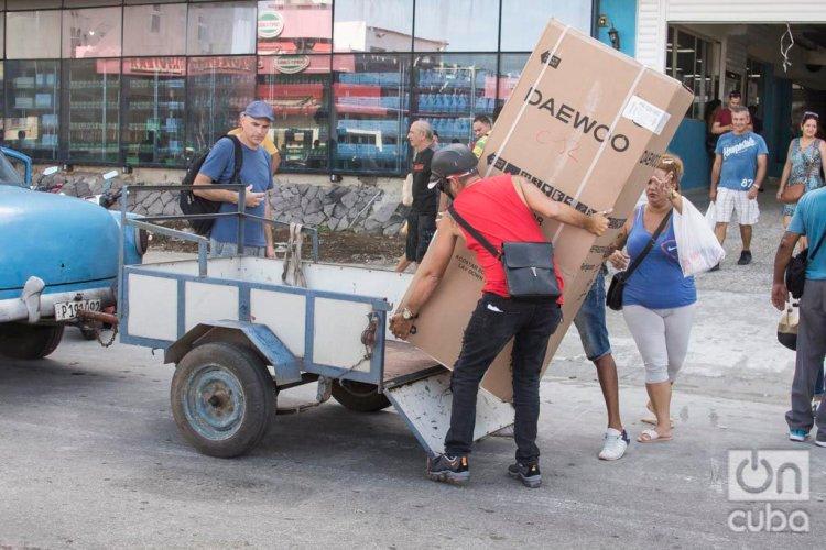 Un hombre sube a un carro un refrigerador comprado el lunes 28 de octubre de 2019, en el centro comercial Galerías de Paseo, en La Habana, en el que este 28 de octubre de 2019 comenzó la venta de equipos electrodomésticos en divisas a través de tarjetas magnéticas asociadas a cuentas bancarias. Foto: Otmaro Rodríguez.