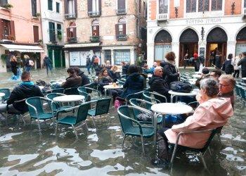 La vida continúa en medio de las inundaciones en Venecia y lugareños y turistas se sientan en un bar, en las mesas de la calle, a pesar de que el agua les sobrepasa los tobillos el 17 de noviembre del 2019. (Emiliano Creeps/ANSA via AP)
