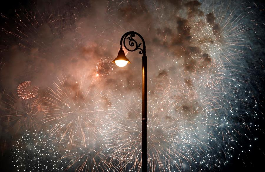 Cielo iluminado por fuegos artificiales tras una farola en La Habana. Foto: EFE/Ernesto Mastrascusa