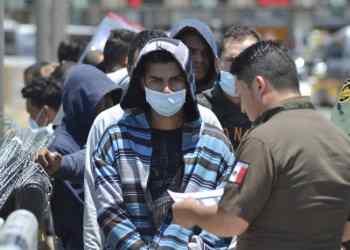 Un oficial de aduanas procesa el retorno a México de un grupo de inmigrantes en la frontera de Laredo, Texas. Foto: AP