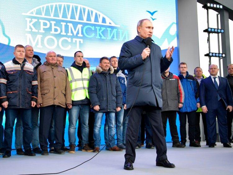 El presidente ruso Vladimir Putin habla con constructores después de viajar a bordo del tren que une a Rusia con la península de Crimea en Taman. Foto: Alexei Nikolsky/Pool Photo vía AP.