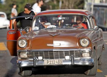 Un grupo de personas suben a un automóvil clásico que funciona como taxi en La Habana (Cuba). Foto: EFE/ Yander Zamora