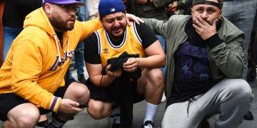 De izquierda a derecha, Alex Fultz, Eddy Rivas y René Alfaro, fanáticos de los Lakes de Los Ángeles, lloran tras enterarse del fallecimiento del exjugador Kobe Bryant, frente al Staples Center, antes de la 62da entrega del Grammy, el domingo 26 de enero de 2020 (AP Foto/Chris Pizzello)