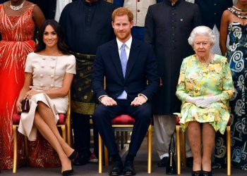 El príncipe Enrique, su esposa Meghan Markle (izq) y su abuela, la reina Isabel II, fotografiados durante una ceremonia en el Palacio de Buckingham el 26 de junio del 2018. En un comunicado enviado el lunes 13 de enero de 2020 la reina Isabel II dijo que accedió a conceder el deseo del príncipe Enrique y Meghan para una vida más independiente en la que residirán parcialmente en Canadá. (John Stillwell/Pool Photo via AP, archivo)