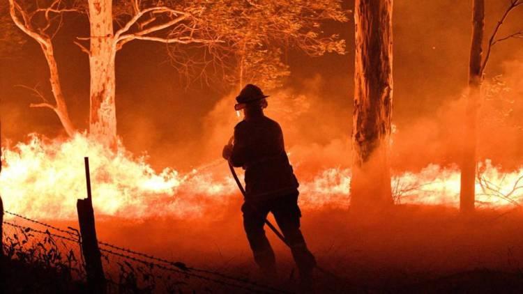 Un bombero trata de apagar el fuego en Nowra, Nueva Gales del Sur, Australia, el martes 2 de enero. Foto: El País
