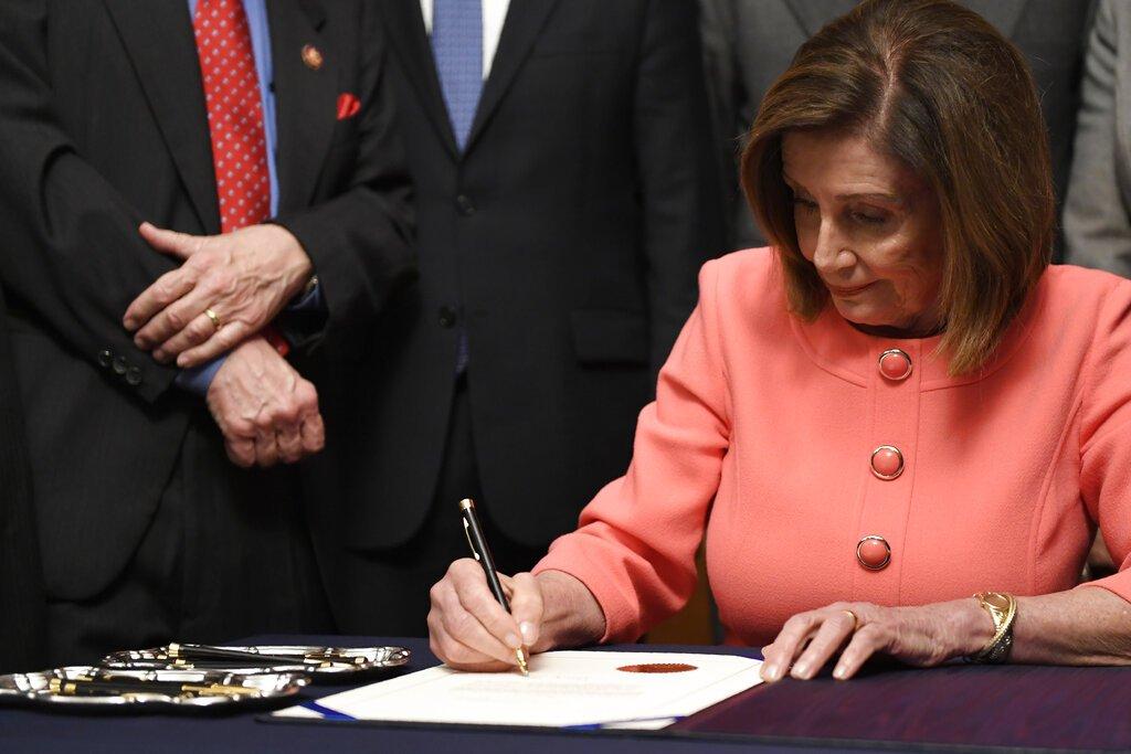 La presidenta de la Cámara de Representantes Nancy Pelosi, firma el acta para enviar dos cargos de juicio político contra el presidente Donald Trump al Senado en el Capitolio, el miércoles 15 de enero de 2020, en Washington. Foto: AP/Susan Walsh