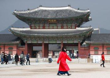 Una mujer con una mascarilla camina por delante del Palacio Gyeongbok, uno de los monumentos más conocidos de Corea del Sur, en Seúl, Corea del Sur, el 22 de febrero de 2020. Foto: Lee Jin-man / AP.