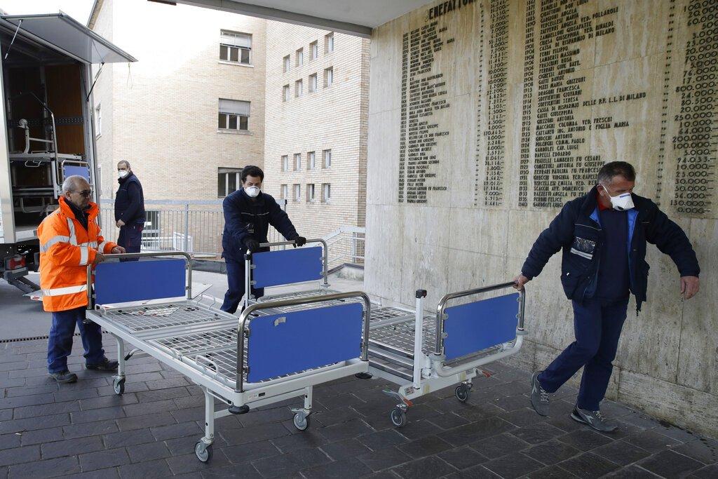 Operarios llevan nuevas camas al interior del hospital de Codogno, cerca de Lodi, en el norte de Italia, el 21 de febrero de 2020. Foto: Luca Bruno / AP.