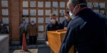 Enterradores colocan el ataúd en su tumba en el cementerio de La Almudena en Madrid, España, el sábado 28 de marzo de 2020. Foto: Olmo Calvo/AP.
