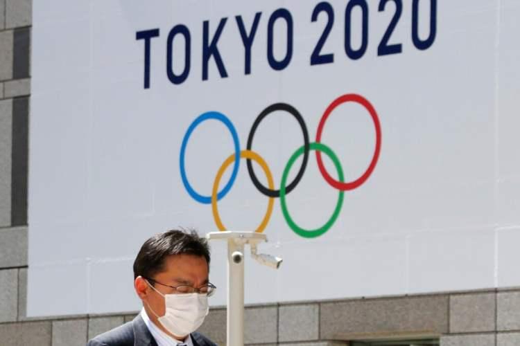 Un hombre con una mascarilla pasa junto a un cartel que anuncia los Juegos Olímpicos de Tokio del 2020, ya pospuestos para el próximo año. Foto: Koji Sasahara / AP / Archivo.